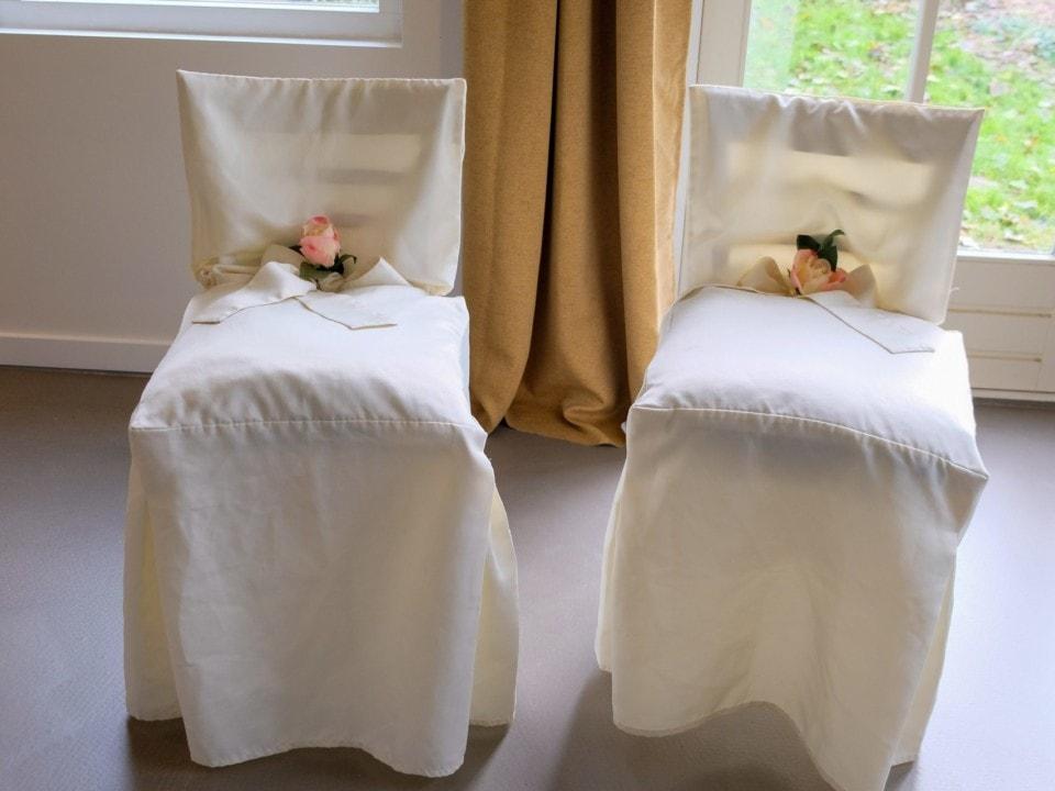 2 witte stoelen met een bloem erop