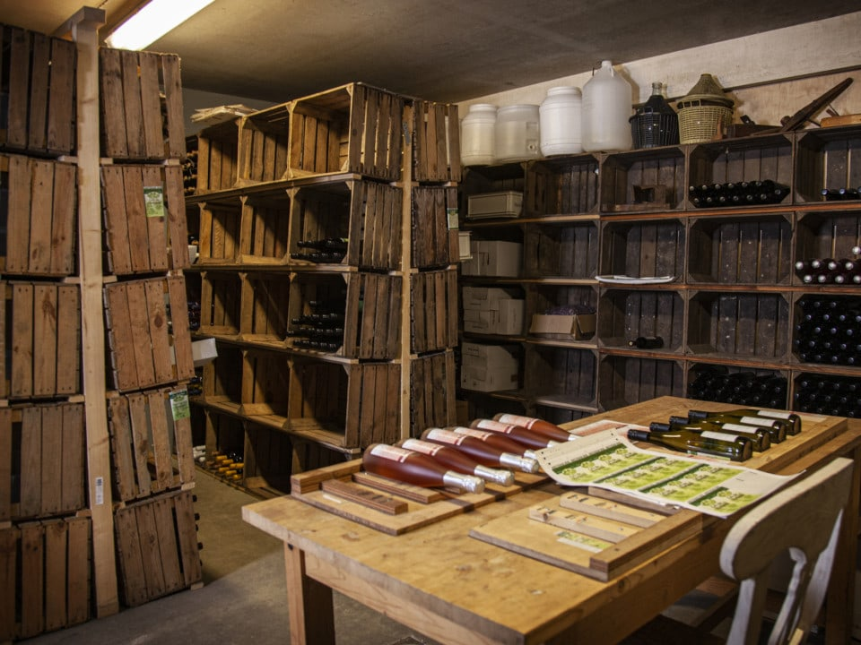 Kasten van houten kratten met wijnflessen en tafel met wijnflessen