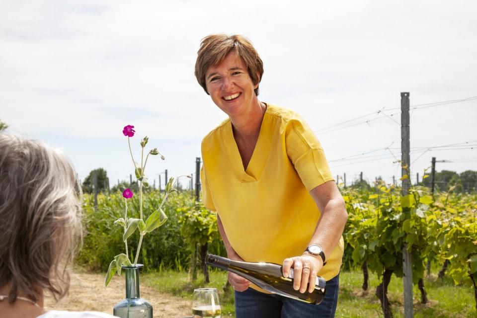 Lachende vrouw (Annelies) die wijn inschenkt